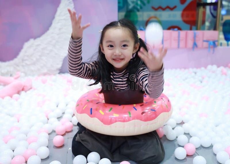 De mooie vrolijke grond van het meisje speelgenoegen op speelplaats royalty-vrije stock afbeelding