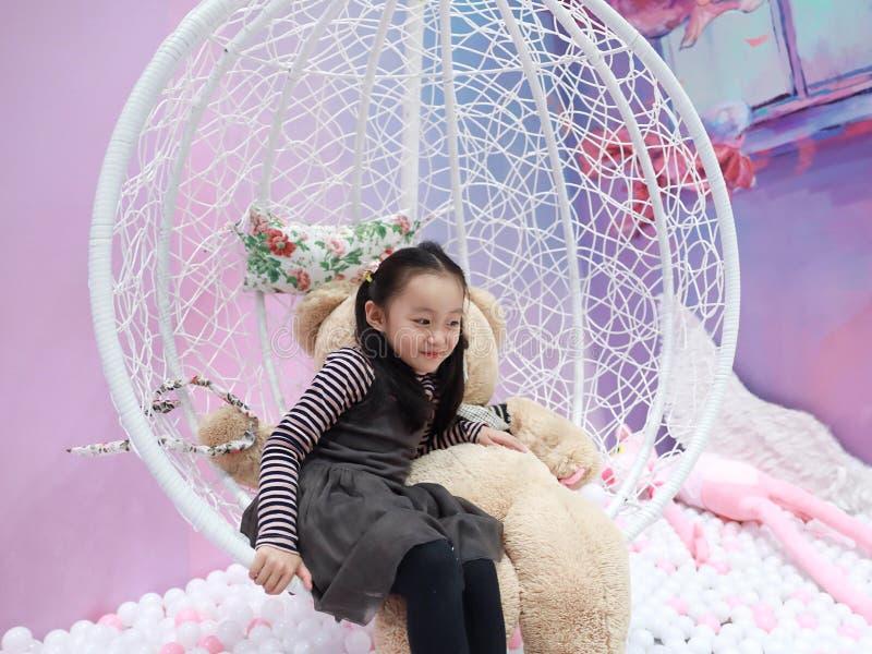 De mooie vrolijke grond van het meisje speelgenoegen op speelplaats royalty-vrije stock foto