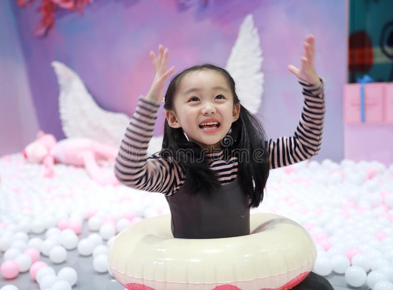 De mooie vrolijke grond van het meisje speelgenoegen op speelplaats royalty-vrije stock afbeeldingen