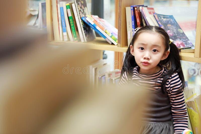 De mooie vrolijke grond van het meisje speelgenoegen op speelplaats stock fotografie