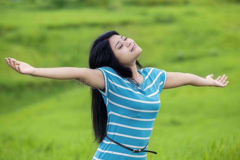 De mooie vrouw ademt verse lucht bij gebied stock fotografie