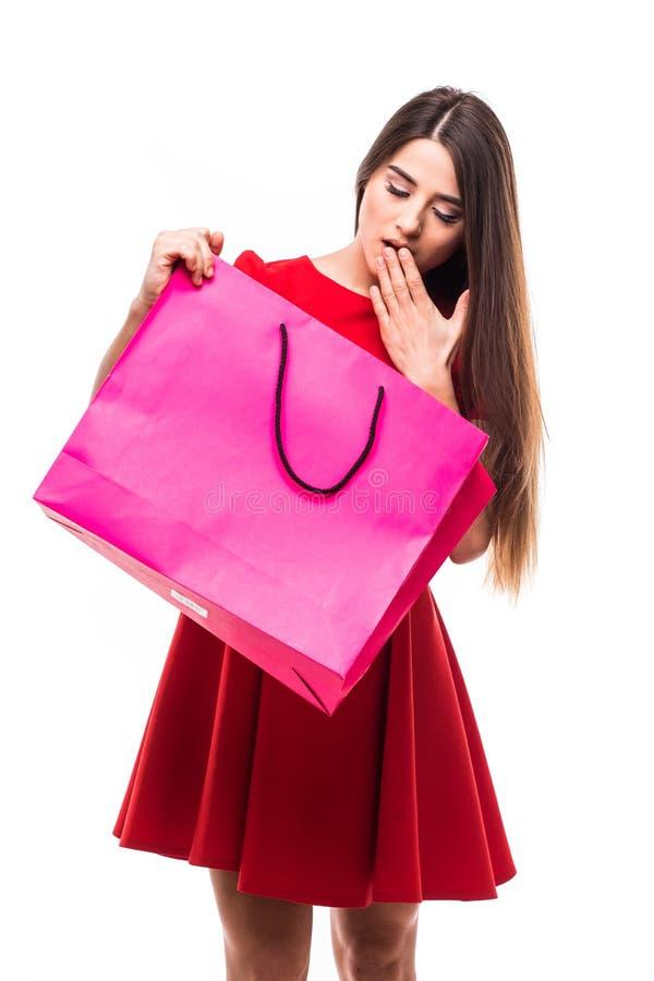 De mooie vrouw bekijkt kleuren shoping zak met gelukkig geschokt gezicht op witte achtergrond stock afbeeldingen