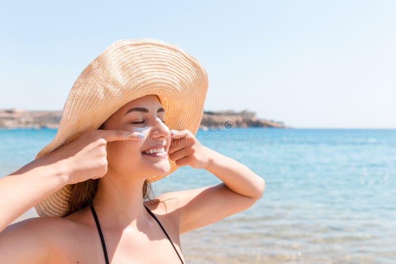 De mooie vrouw beschermt haar huid op gezicht met sunblock bij het strand royalty-vrije stock afbeeldingen