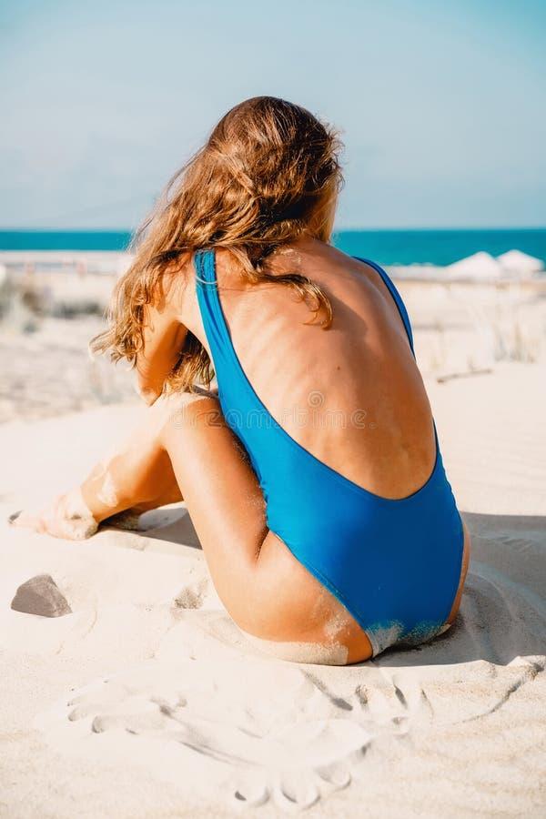 De mooie vrouw in blauwe bikini zit op tropisch strand Het lichaam van de de zomervrouw stock foto