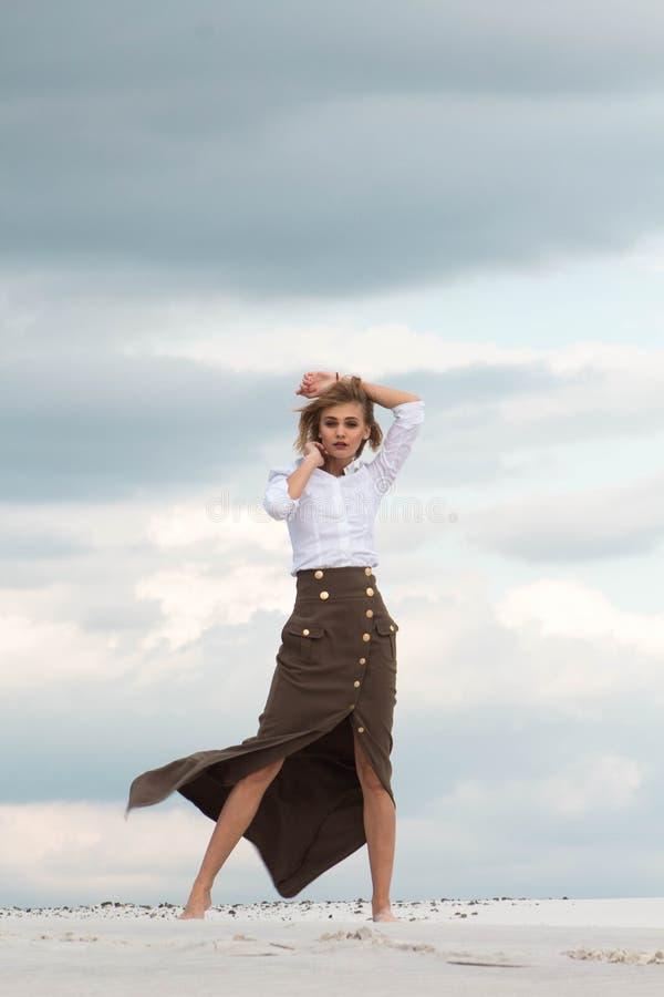 De mooie vrouw danst elegant in de woestijn stock afbeelding