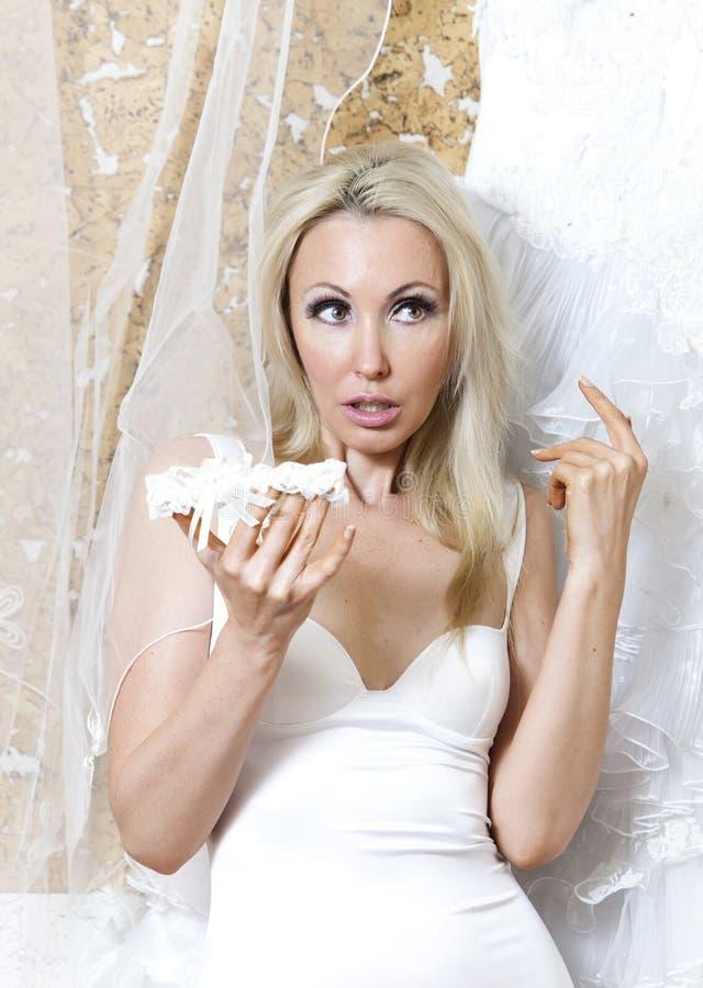 De mooie vrouw, de bruid, met een kouseband dichtbij een huwelijkskleding stock afbeelding
