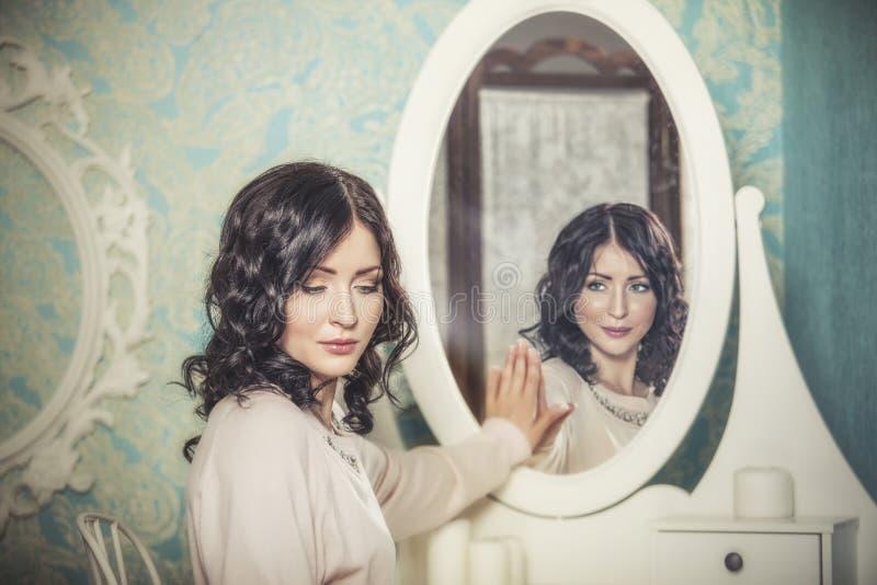 De mooie vrouw in de spiegel wees magisch op de glimlachen stock foto