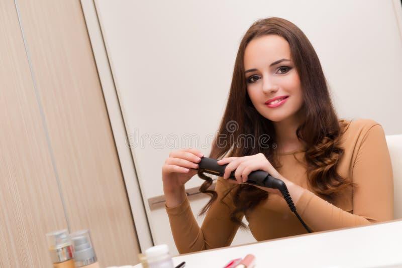 De mooie vrouw die haar haar doen die voor partij voorbereidingen treffen royalty-vrije stock afbeelding