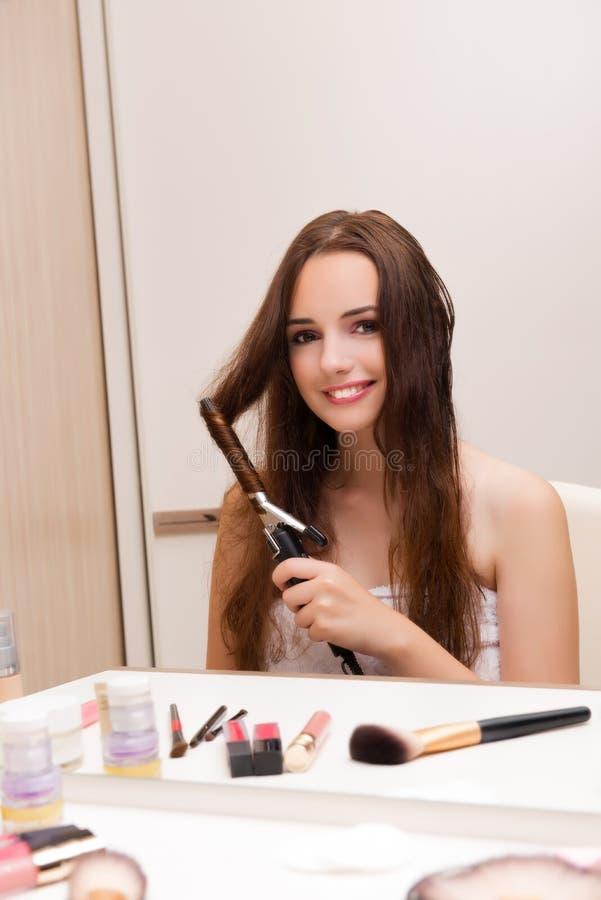 De mooie vrouw die haar haar doen die voor partij voorbereidingen treffen royalty-vrije stock foto's