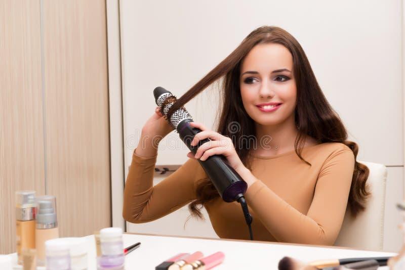De mooie vrouw die haar haar doen die voor partij voorbereidingen treffen stock fotografie