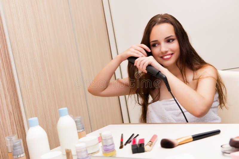 De mooie vrouw die haar haar doen die voor partij voorbereidingen treffen royalty-vrije stock fotografie