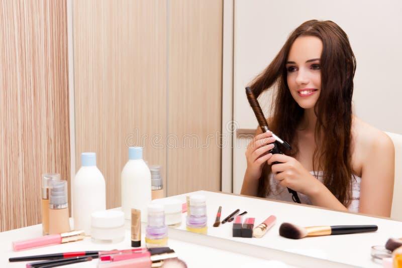 De mooie vrouw die haar haar doen die voor partij voorbereidingen treffen stock foto's