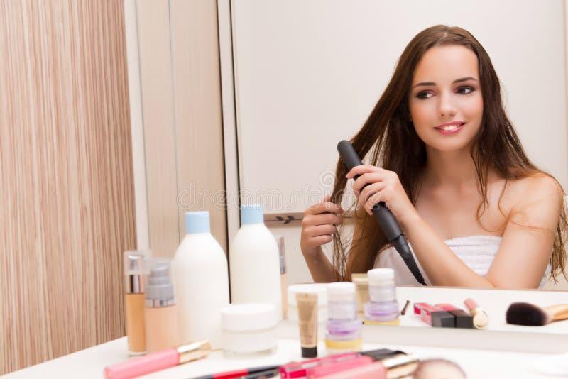 De mooie vrouw die haar haar doen die voor partij voorbereidingen treffen stock foto