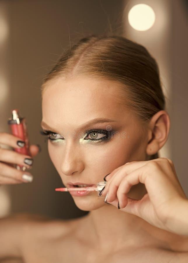 De mooie vrouw die lippenstift toepassen polijst, studiospruit royalty-vrije stock foto