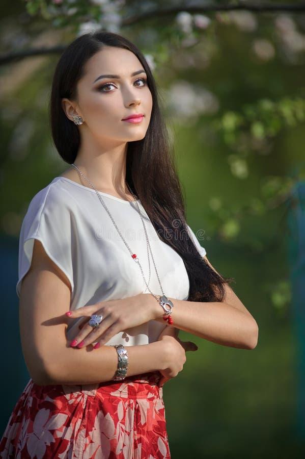 De mooie vrouw die van Yong luxetoebehoren in de bloeiende lente dragen royalty-vrije stock afbeelding