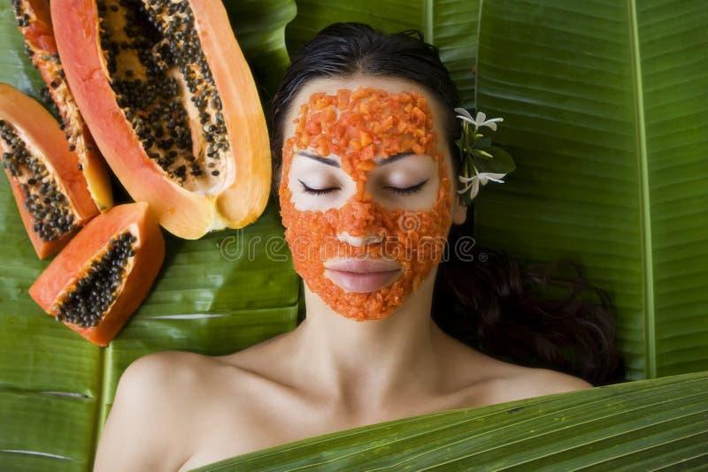 De mooie vrouw die vers papaja gezichtsmasker hebben schrijft in verse pap stock afbeeldingen