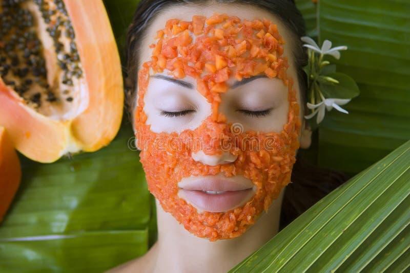 De mooie vrouw die vers papaja gezichtsmasker hebben schrijft in verse pap stock foto