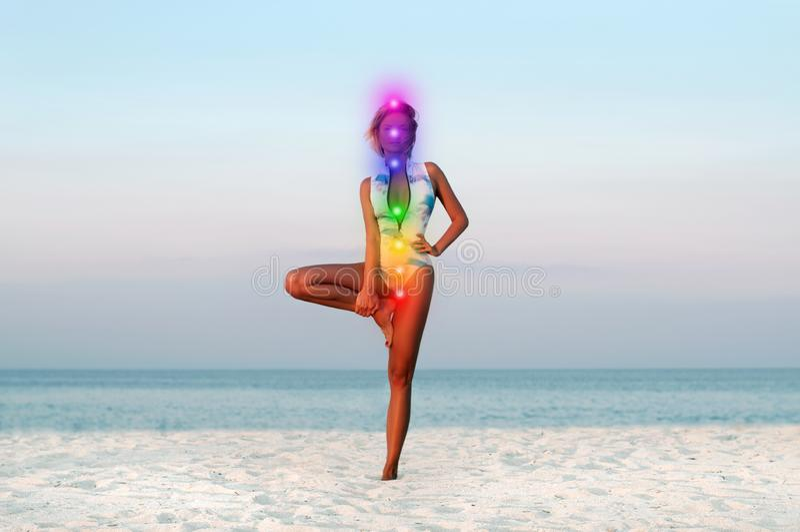 De mooie vrouw die yogaboom doen stelt op het strand stock afbeelding