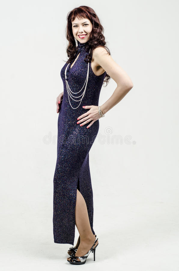 De mooie vrouw in donkerblauwe kleding met lovertjes snakt cocktail royalty-vrije stock afbeeldingen