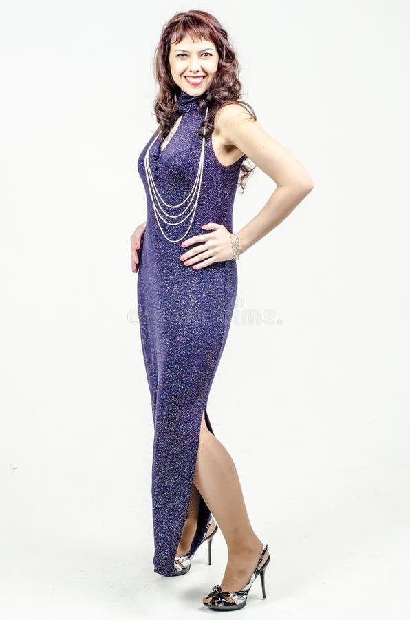 De mooie vrouw in donkerblauwe kleding met lovertjes snakt cocktail stock afbeelding