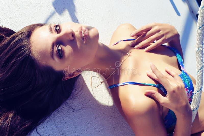 De mooie vrouw draagt blauwe bikini, ontspannend op jacht in het overzees stock afbeeldingen