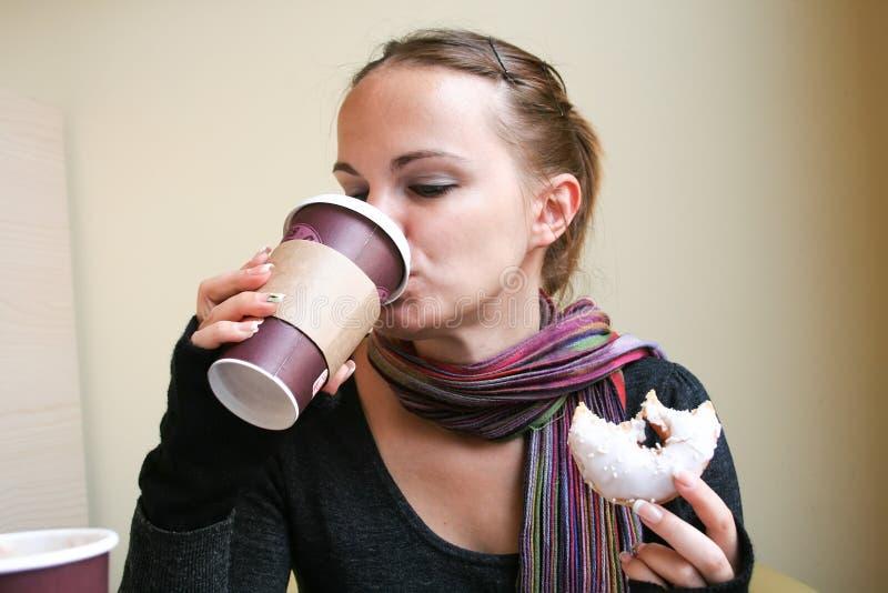 De mooie vrouw drinkt koffie van een kartonkop en houdt een gebeten doughnut in haar andere hand royalty-vrije stock fotografie