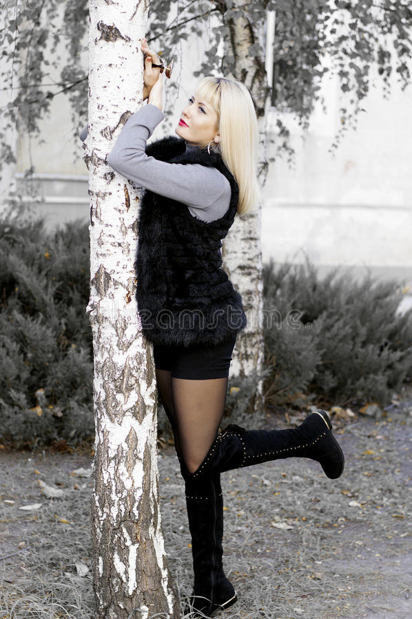 De mooie vrouw in een bontjas met de opgeheven voet leunde ag stock foto's