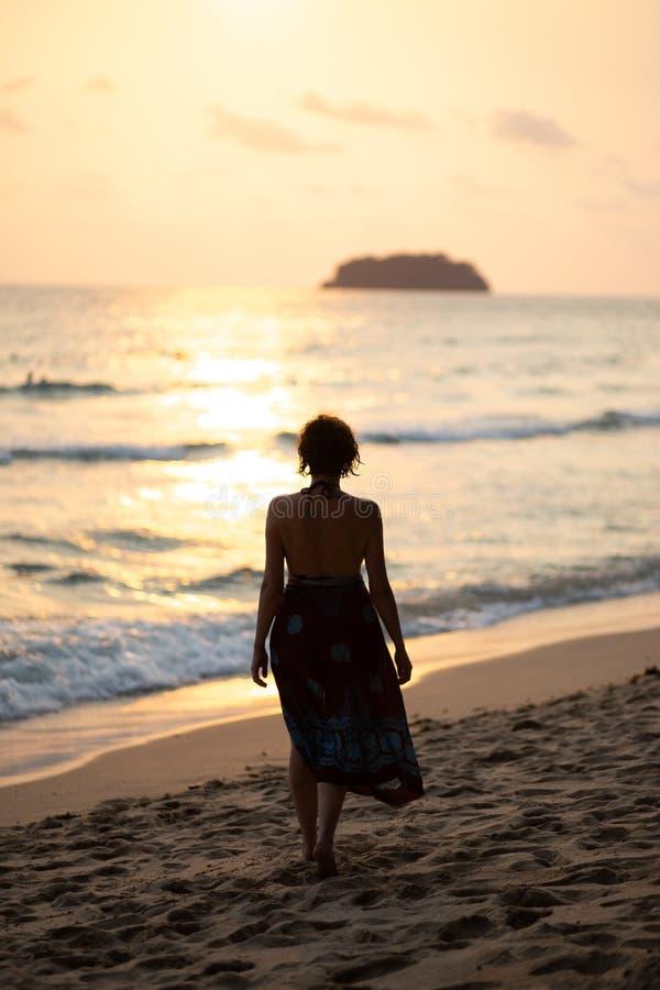 De mooie vrouw in een kleurrijke de zomerkleding die op het strand van Thailand Ko Chang met mooi wit lopen verzendt tijdens a stock fotografie