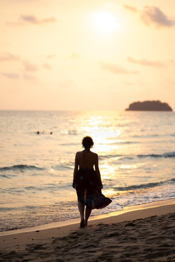 De mooie vrouw in een kleurrijke de zomerkleding die op het strand van Thailand Ko Chang met mooi wit lopen verzendt tijdens a stock afbeelding
