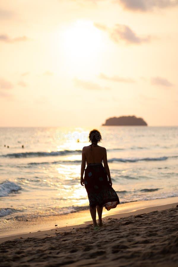 De mooie vrouw in een kleurrijke de zomerkleding die op het strand van Thailand Ko Chang met mooi wit lopen verzendt tijdens a stock foto's