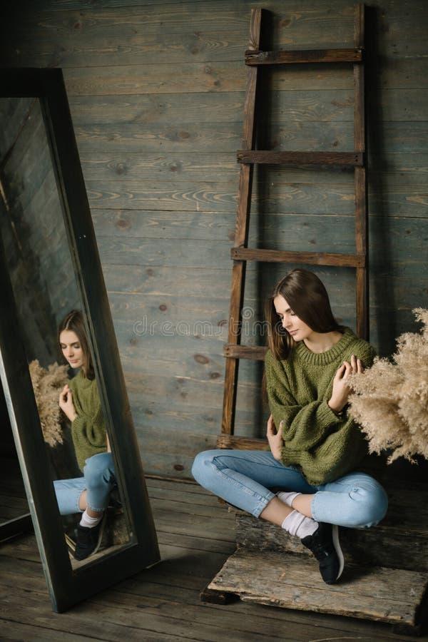 De mooie vrouw in een moeras breide comfortabele sweater met hooisamenstelling dichtbij de oude houten muurachtergrond met ladder royalty-vrije stock afbeeldingen