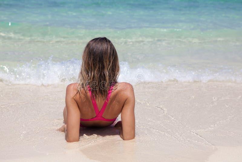 De mooie vrouw in een roze zwempak ligt op wit zandstrand stock foto