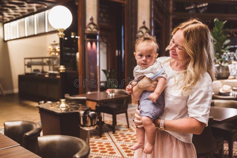 De mooie vrouw in een witte kleding met haar zoon heeft een rust in de koffie in het hotel van Parisi Udvar in V-district in Boed stock foto's
