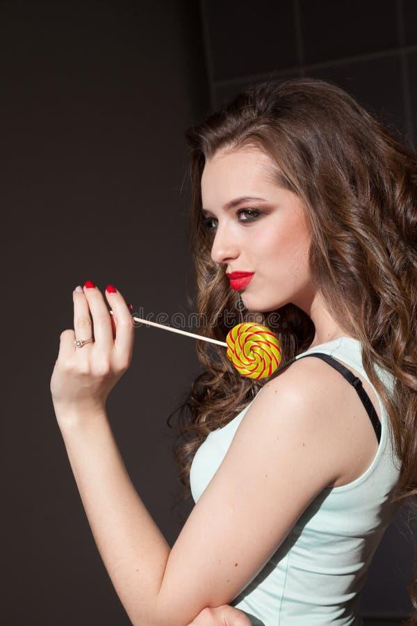 De mooie vrouw eet de zoete smakelijke snoepjes van de suikergoedlolly stock foto's