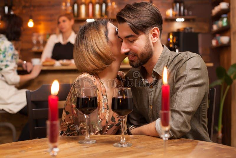 De mooie vrouw fluistert aan haar knap vriendoor hoeveel zij van hem houdt stock afbeelding