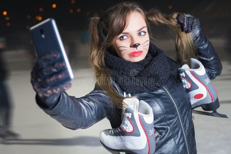 De mooie vrouw gekleed in kattenkostuum, maakt selfie stock fotografie