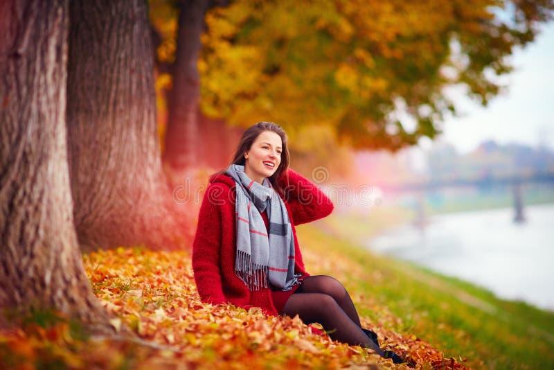 De mooie vrouw geniet van de herfst in park stock afbeelding