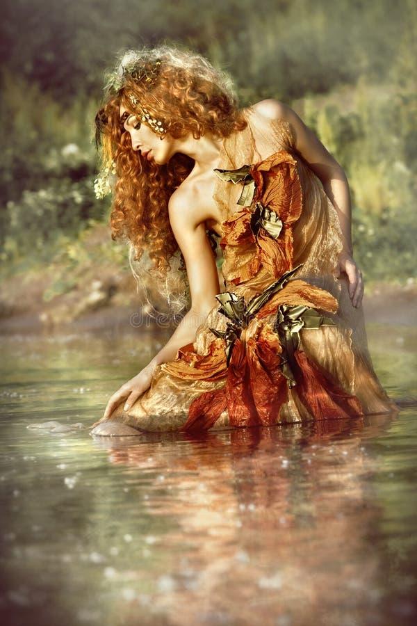 De mooie vrouw geniet van het water. stock afbeelding