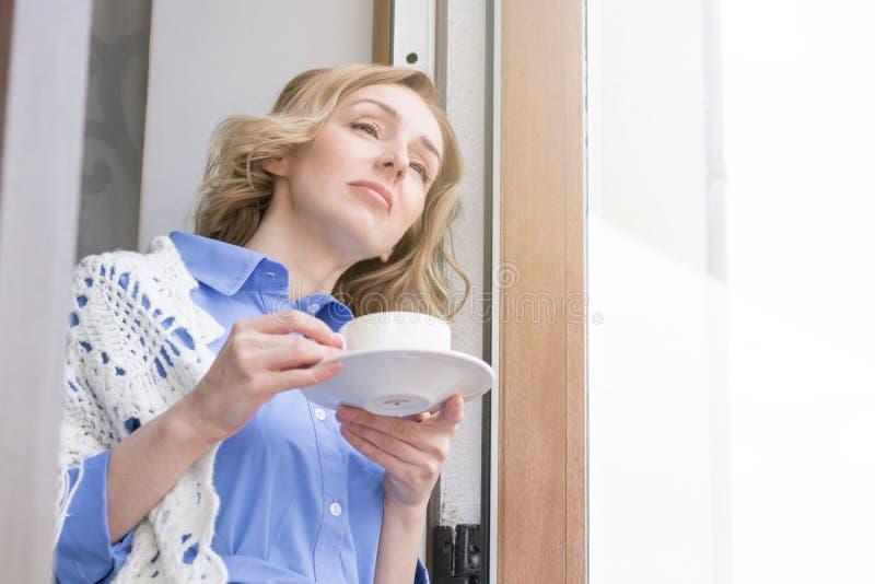 De mooie Vrouw geniet van Koffie en denkt royalty-vrije stock foto's