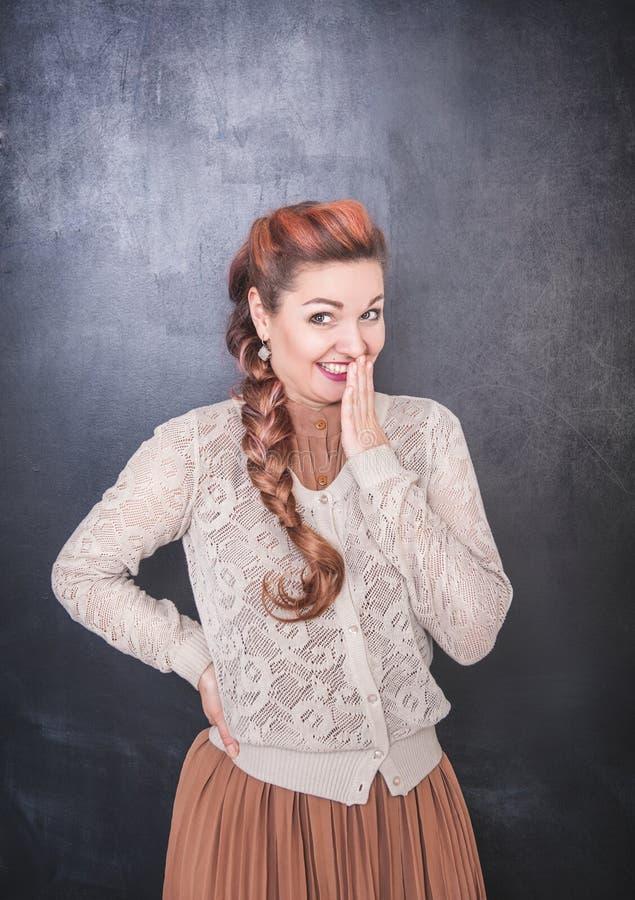 De mooie vrouw giecheelt op bordachtergrond stock fotografie