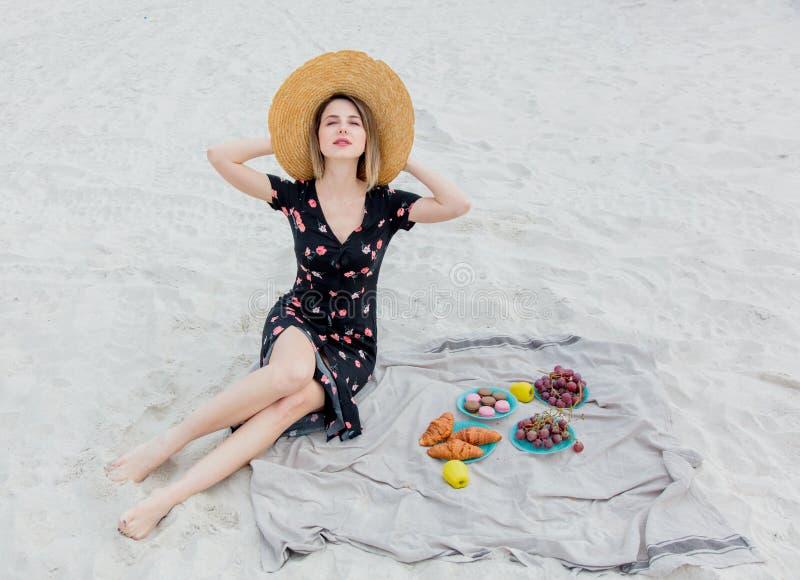 De mooie vrouw heeft een rust op een strand dichtbij een overzees stock afbeelding