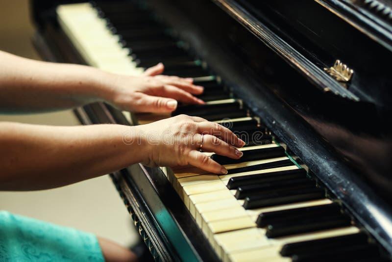 De mooie vrouw het spelen piano, sluit van vrouw overhandigt omhoog speelpi stock foto's