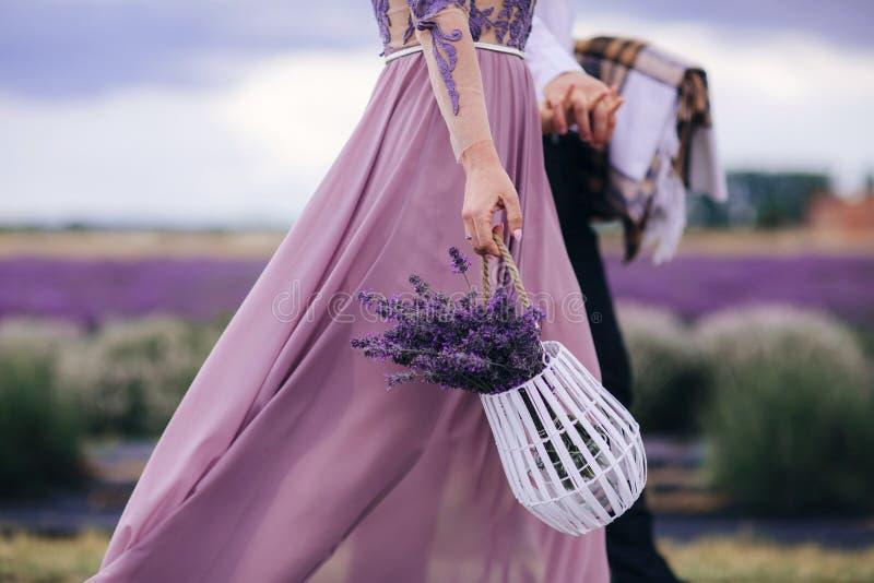 De mooie vrouw houdt boeket van bloemenlavendel in mand terwijl lopen openlucht door tarwegebied in de zomer stock foto