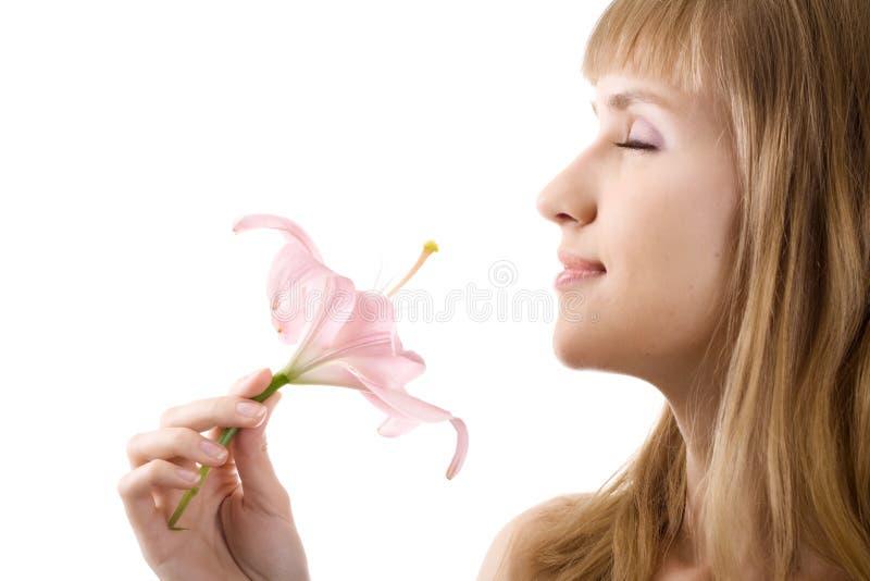 De mooie vrouw inhaleert geïsoleerdt aroma van lelie stock afbeelding