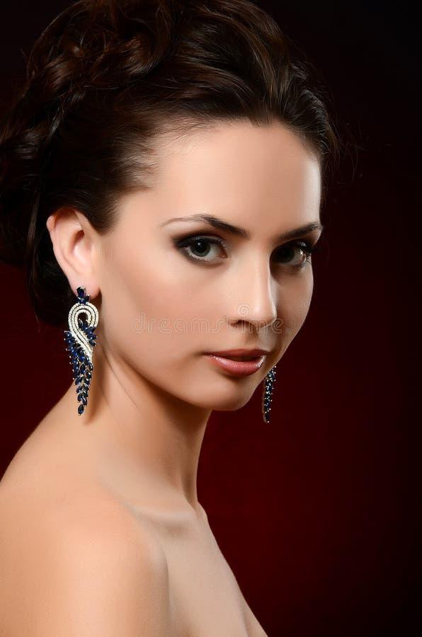 De mooie vrouw in juwelenoorringen stock fotografie