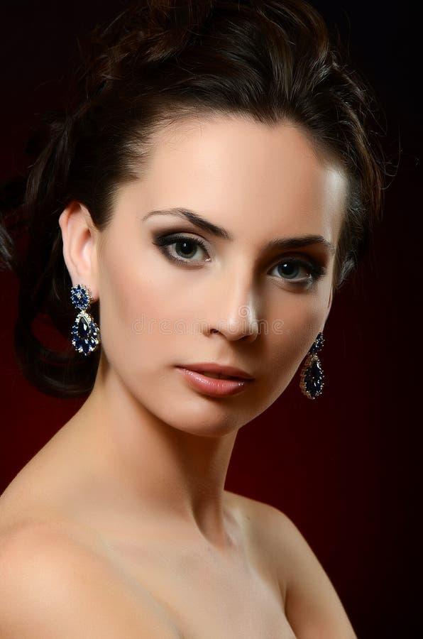De mooie vrouw in juwelenoorringen royalty-vrije stock foto