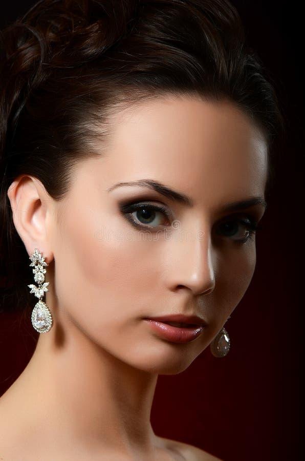 De mooie vrouw in juwelenoorringen stock afbeeldingen