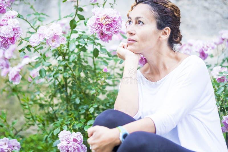 De mooie vrouw kijkt aan haar kant met bloemachtergrond royalty-vrije stock fotografie