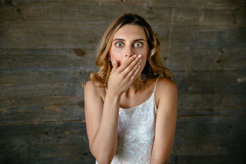 De mooie vrouw kijkt geschokt met de hand behandelend haar mond stock afbeelding