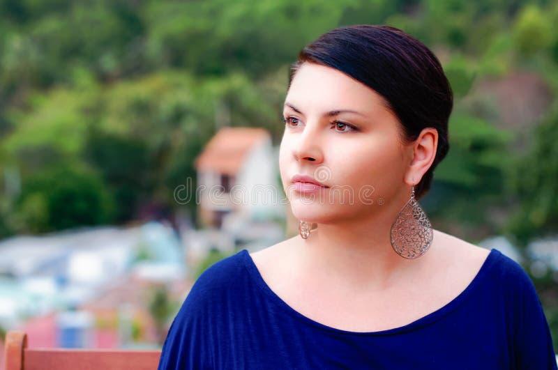 De mooie vrouw kijkt zijdelings, stadsachtergrond royalty-vrije stock fotografie